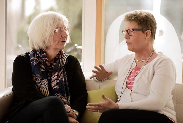 Två kvinnor sitter i en soffa vända mot varandra, i samtal.