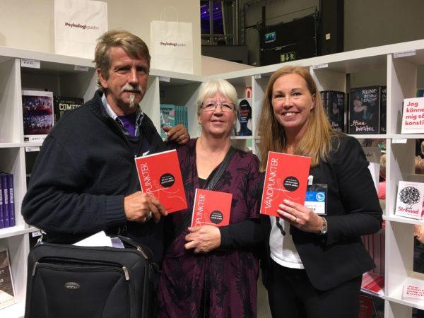 Tre personer, en man och två kvinnor, poserar med boken i händerna.